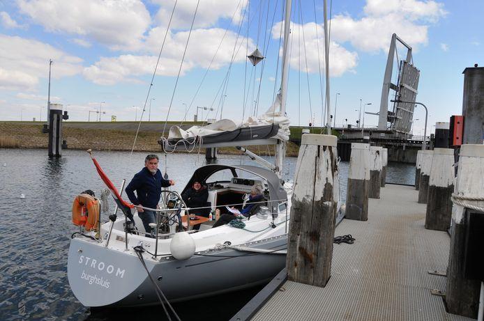 Marco en Gerwin van Vulpen, en Annelies Boot wachten geduldig tot ze door de Grevelingensluis kunnen varen. Op de achtergrond de kapotte brug, die al vijf maanden omhoog staat.