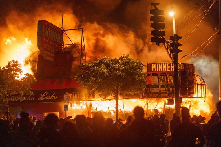 Een drankwinkel nabij het politiebureau gaat in vlammen op. Beeld Kerem Yucel / AFP