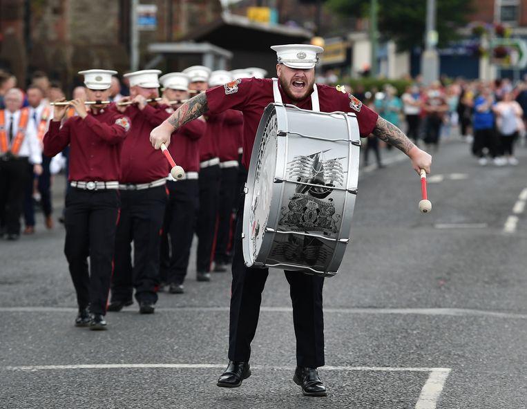 In Belfast roert de drummer van de Shankill Protestant Flute band de trom tijdens de  traditionele parade gisteren. Protestanten in Noord-Ierland herdenken jaarlijks op 12 juli de overwinning van hun protestantse koning William III op de zittende katholieke vorst James II in de slag bij de rivier de Boyne in 1690.  Beeld Getty Images