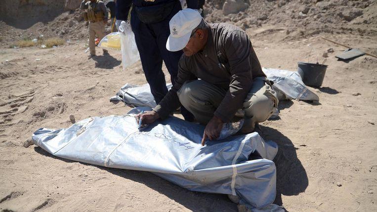 Een lid van het forensische team schrijft een code op een van de getraceerde lichamen bij Tikrit. Beeld Reuters