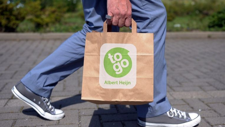Een man met een tasje van Albert Heijn to go in Mettmann, Duitsland. Beeld EPA