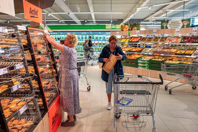 Lia Paijmans (links) lepelt haar broodjes uit de rekken in de nieuwe Lidl van Oisterwijk.