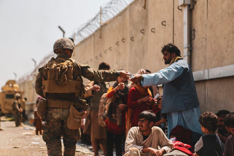 Amerikaanse troepen staan vluchtelingen bij op de internationale luchthaven van Kaboel. Beeld Photo News