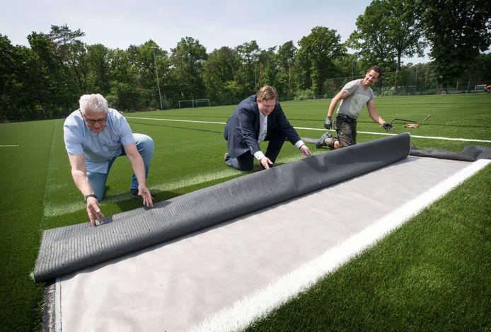 Secretaris Jan Andrik (l.) van VV Rijen, wethouder David Vermorken helpen aannemer John Papakonstantinu met het leggen van de laatste mat kunstgras.