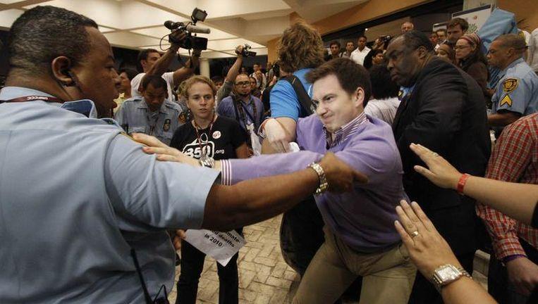 Security-agenten proberen een actievoerder uit het conferentiegebouw in Cancún te houden. Beeld REUTERS