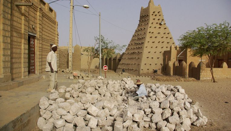 Straatwerkers nabij een moskee in de typische bouwstijl van van Timboektoe Beeld ap