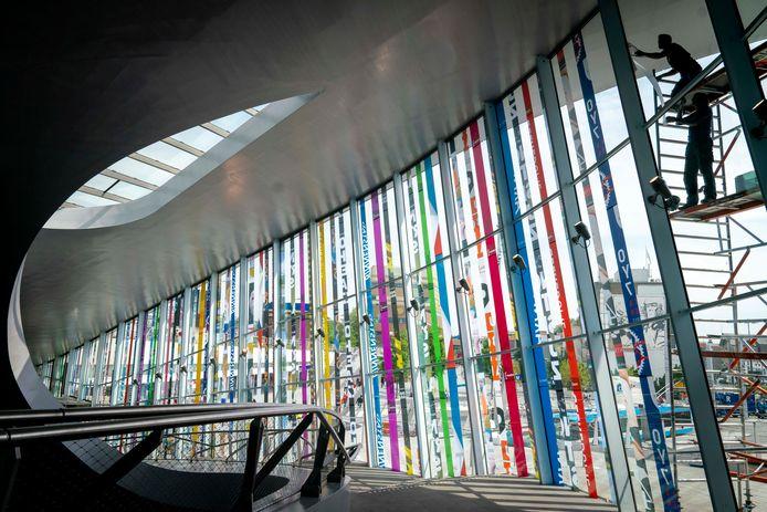 De banieren voor State of Fashion worden bevestigd aan de glazen gevel van het Arnhemse stationsgebouw.
