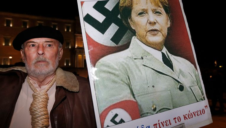 Een man toont een poster van Angela Merkel bij demonstraties voor het Griekse parlement in november vorig jaar. Beeld AP