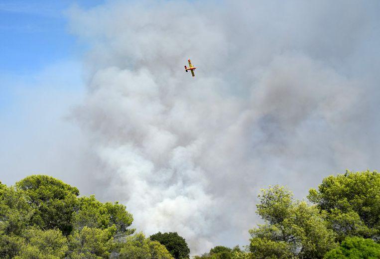 Een blusvliegtuig Canadair CL 415  vliegt dinsdag boven een bosbrand in Gonfaron, in het Zuid-Franse departement Var. Beeld AFP