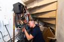 Een monteur is bezig in de wijk Linie van Breda met het monteren van de unit van het warmtenet in de kelder.