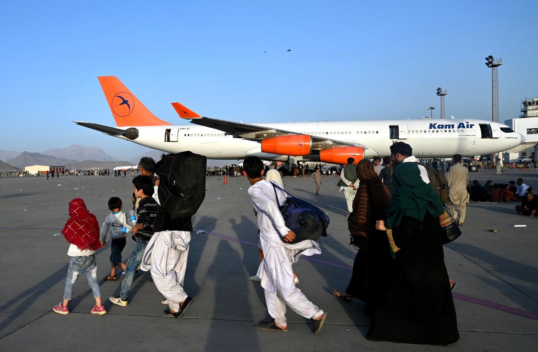Afghaanse families op het tarmac van de luchthaven van Kaboel. Beeld AFP