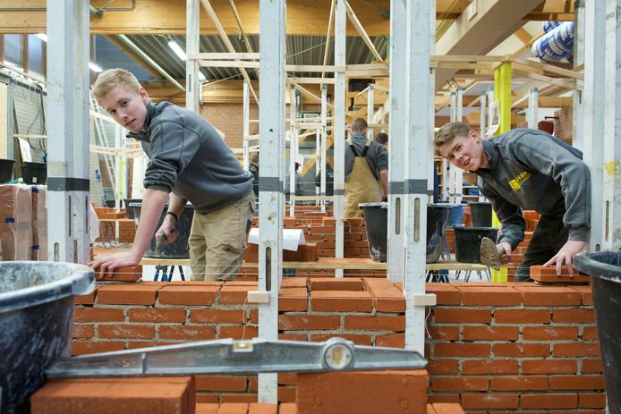 Roy Janssen (links) en Jelle Maters van het OBC in Huissen nemen deel aan de regionale voorronde van het NK-Metselen bij leerbedrijf ReVaBo in Oosterbeek.