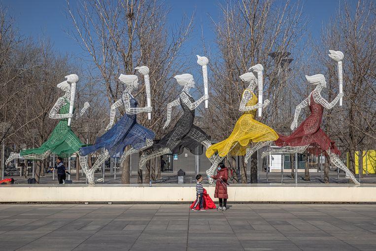 Een moeder en zoon voor het Olympisch Park in de Chinese hoofdstad Beijing, waar van 4 tot 20 februari de Olympische Winterspelen zijn gepland. Beeld EPA