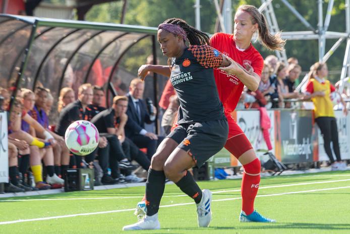 Kaycie Tillman  van PSV schermt de bal af voor Bente Jansen.