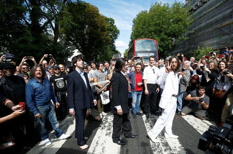Een Beatles-coverband loopt over het zebrapad van Abbey Road, afgelopen augustus.  Beeld Reuters