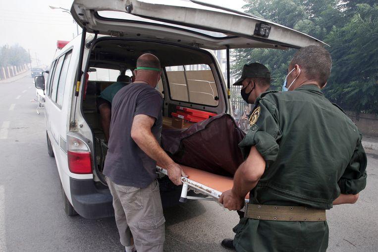 Het lichaam van een dode soldaat wordt geborgen bij Tizi Ouzou. Beeld AP