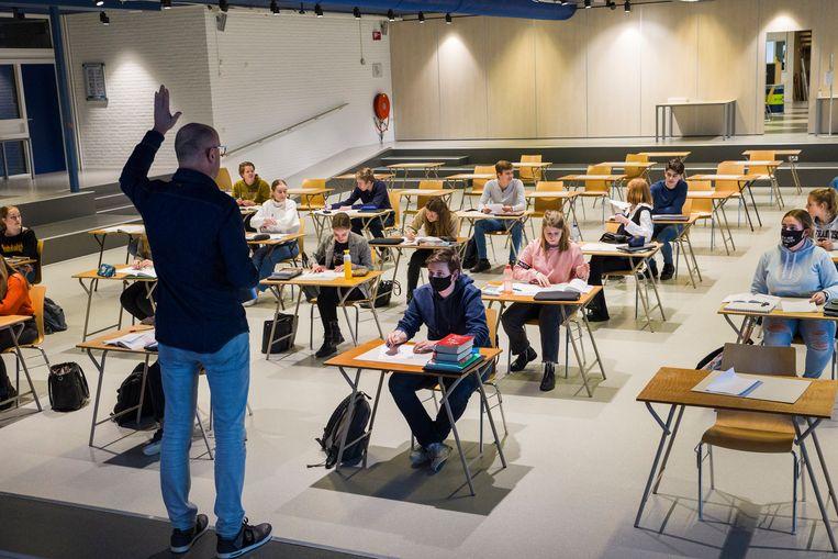 Een eindexamenklas krijgt les in de aula om afstand te kunnen bewaren.  Beeld Arie Kievit
