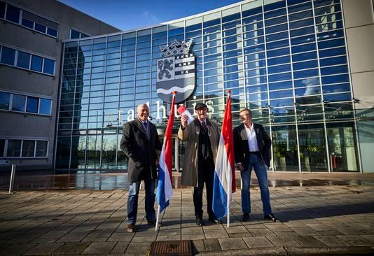 Drie mannen hebben een Nederlandse vlag aangeboden bij het loket van het Stadhuis in Spijkenisse, zodat deze in de raadszaal opgehangen kan worden.