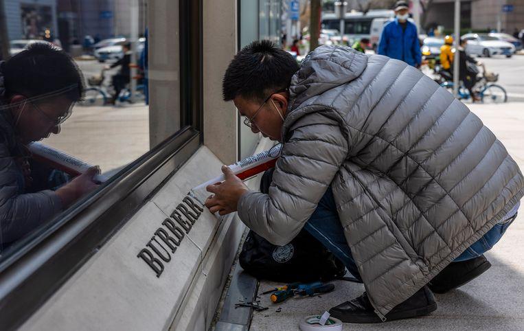 Een man repareert een beschadigd logo van een winkel van de Britse keten Burberry in Shanghai. Burberry ligt, net als andere kledingbedrijven, in China onder vuur vanwege hun kritiek op de behandeling van Oeigoeren in de provincie Xinjiang.  Beeld EPA