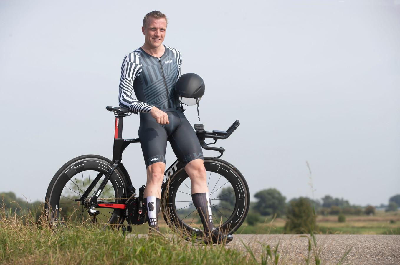 Robert Braam met zijn tijdritfiets op de dijk in Wageningen.