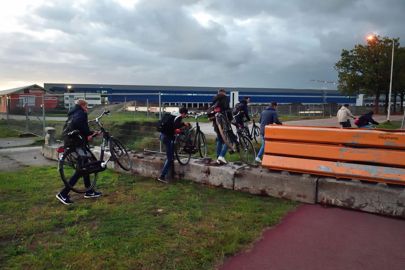 Klauterend over de afzetting vinden de fietsers toch nog de kortste route langs de Gastelseweg.