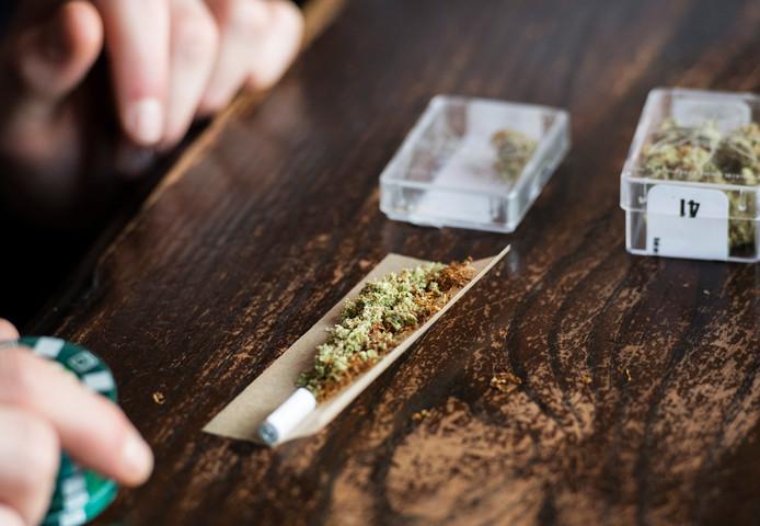 Een bezoeker van een coffeeshop rolt een joint.