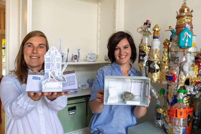 Eva Luijkx (re) en Gertrude van der Linden maken opvouwbare papieren maquettes als souvenirs die te koop zijn bij musea.