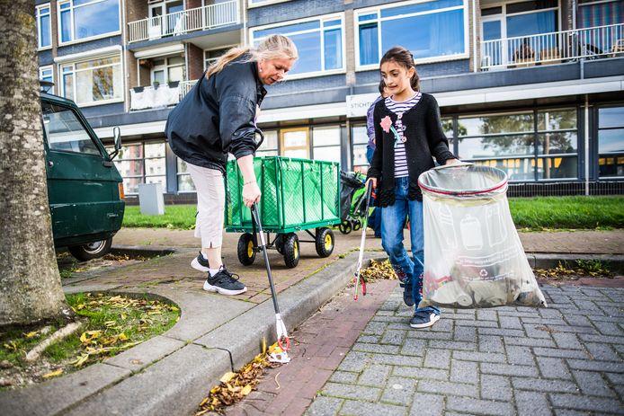 Vrijwilligers van Heel Arnhem Schoon rapen bij een eerdere gelegenheid zwerfafval in Malburgen, met bij de hand de kar voor vervoer van materialen en vuilniszakken.