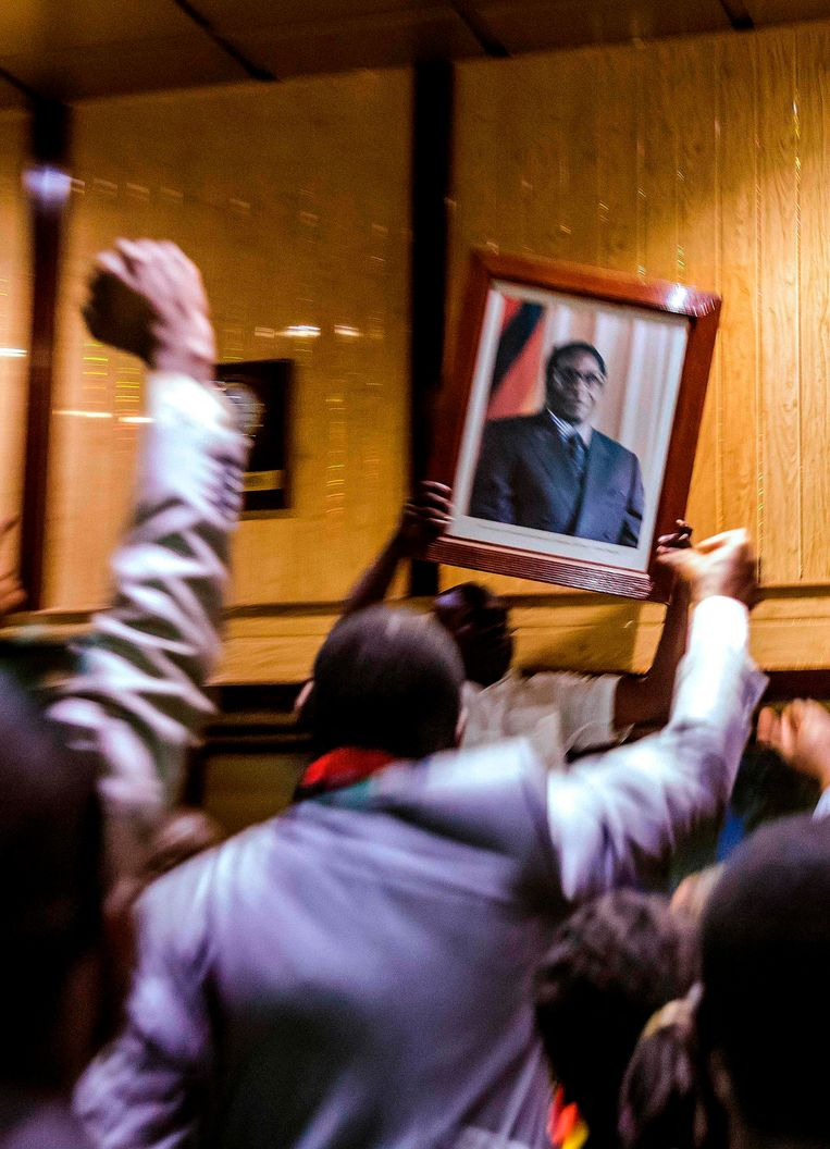 People remove, from the wall at the International Conference centre, where parliament had their sitting, the portrait of former Zimbabwean President Robert Mugabe after his resignation on November 21, 2017 in Harare. Beeld AFP