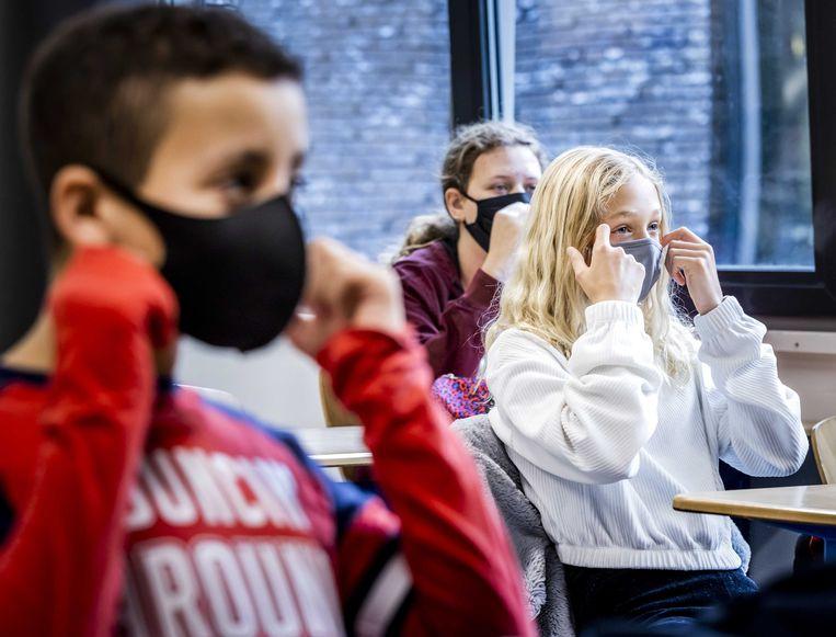 Leerlingen van een middelbare school dragen mondkapjes in de klas. Het dragen van mondkapjes is op veel scholen verplicht, sinds de nieuwe stijging van het aantal coronabesmettingen.  Beeld ANP