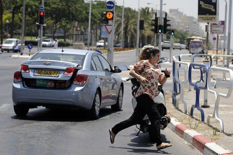 Een vrouw rent door de Israëlische stad Ashdod, die wordt aangevallen door raketten van de Palestijnen. Beeld afp
