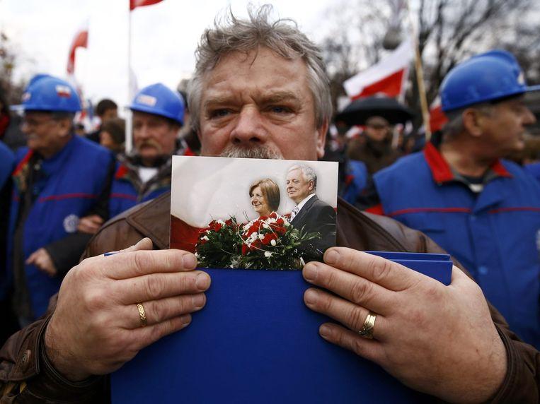 Een man houdt tijdens een demonstratie een foto vast van Lech Kaczynski, tweelingbroer van Jaros¿aw Kaczy¿ski en medeoprichter van regeringspartij Prawo i Sprawiedliwo¿¿. Hij kwam samen met zijn vrouw om het leven tijdens een vliegtuigongeval. Beeld reuters