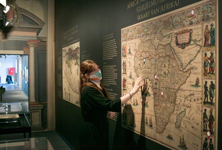 Curator Jolien Van den Bossche  toont een kaart van Afrika uit de 'Atlas Maior'. Het is een van de 594 handgekleurde kaarten in het duurste meerdelige boek dat in de zeventiende eeuw over de toonbank ging.  Beeld JVS