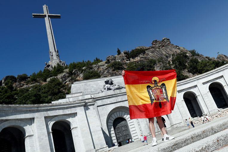Iemand houdt een Spaanse vlag omhoog uit het tijdperk van Franco in 'De Vallei van de Gevallenen'. Beeld EPA
