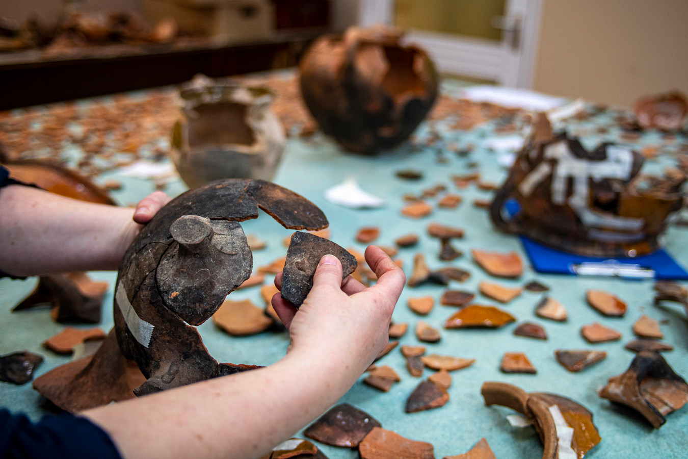 In een van de werkkamers puzzelen vrijwilligers met scherven voor een reconstructie van oud aardewerk.