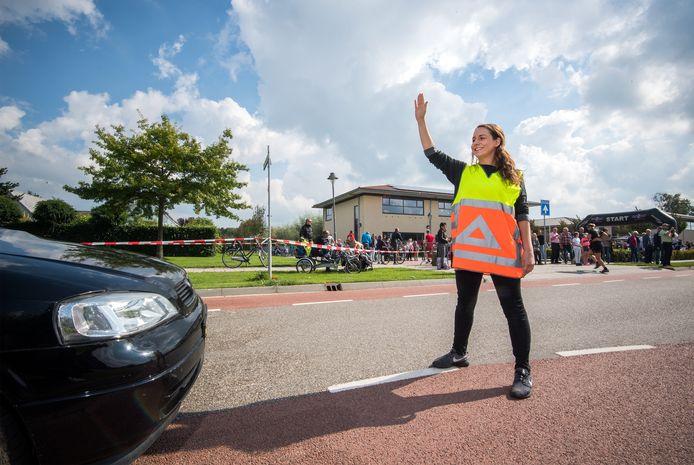 Een verkeersregelaar bij de Brede School tijdens de vierde HeteRun in 2019.