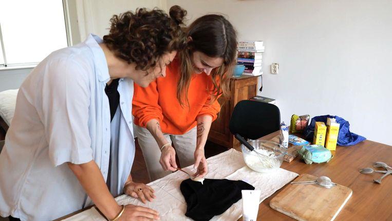 Lize Korpershoek en schrijfster Daan Borrel aan de slag in de keuken: ze proberen met slagroom, handcrème, eieren en lijnzaad de structuur van cervixslijm te benaderen. Beeld  VPRO