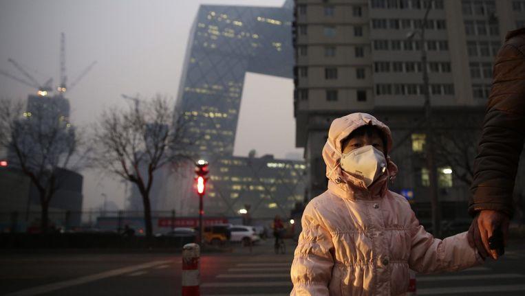 Een meisje draagt een mondkapje tegen de smog in Peking. Beeld epa