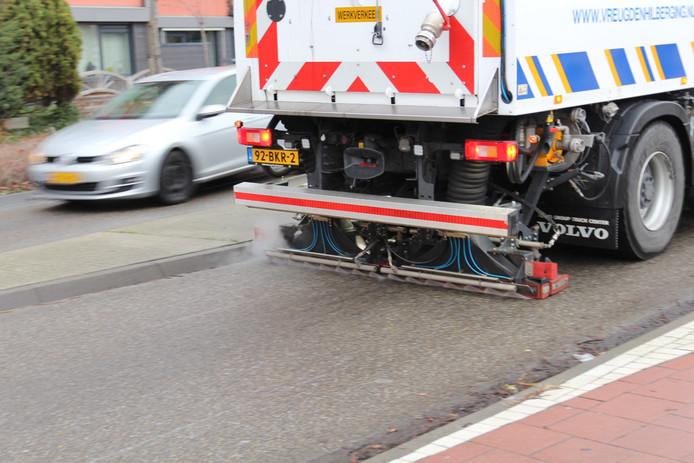 Een schoonmaakwagen maakt de met olie besmeurde wegen in Wateringen schoon.
