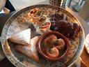 Van bovenaf met de klok mee: Adana kebab, pittig gekruid kalfsgehakt, verpakt in een wrap, met salsasaus en yoghurt met knoflook, spare ribs met heerlijk gemarineerd vlees dat zoals het hoort van de botjes valt,  grote garnalen met knoflook en filodeeg gevuld met Marokkaans gekruide stukjes kip (briwat)