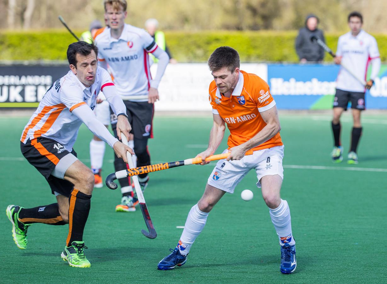 Thierry Brinkman (Bldaal) met links Niek van der Schoot (Oranje Rood)   tijdens de hoofdklasse hockeywedstrijd  Bloemendaal-Oranje Rood  (3-1).
