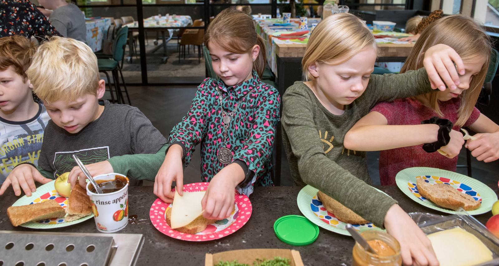Emma van de Brug (m) ontbijt met de officiële burgemeestersketting, die ze tijdens het Nationaal Schoolontbijt omgehangen kreeg van burgemeester Henk Lambooij.