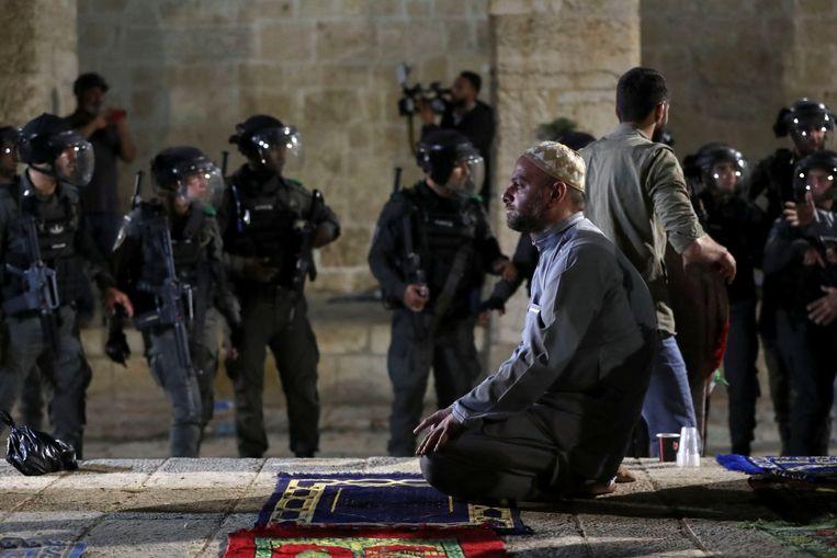 Een Palestijnse man bidt in de Oude Stad terwijl om hem heen de Israëlische politie zich verzamelt.  Beeld REUTERS