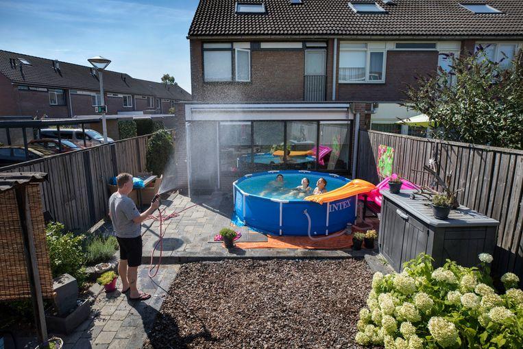 In Elst houdt Jacco Danen het zwembad schoon. Zijn vrouw en dochters liggen erin. Beeld Werry Crone