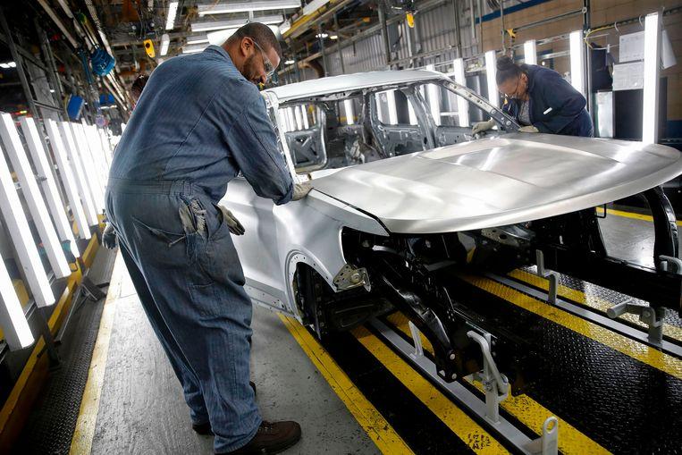Arbeiders in de gerenoveerde fabriek van autobedrijf Ford in Chicago.  Beeld AFP