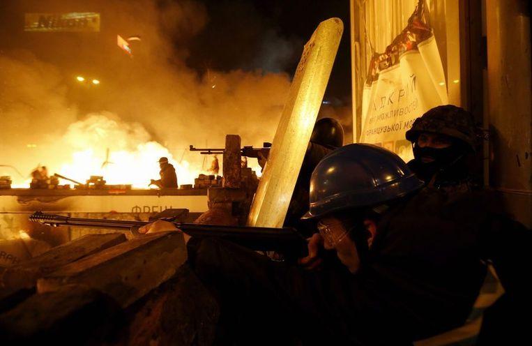 Betogers richten hun wapens op de oproerpolitie, Kiev, in de nacht van dinsdag op woensdag. Beeld reuters