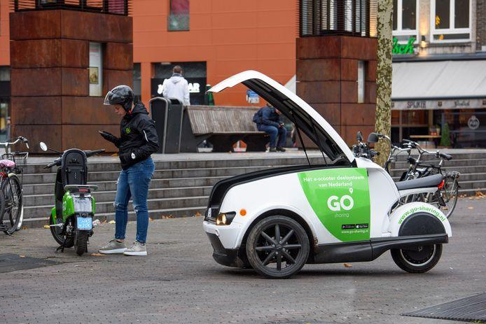 Een medewerker van Go-Sharing controleert een scooter die op het Catharinaplein is geparkeerd.