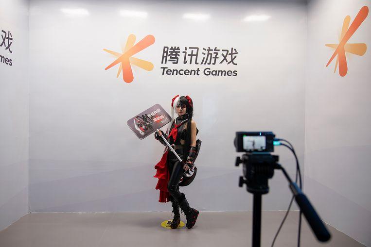 Een cosplay-fan laat tijdens de China Digital Entertainment Expo and Conference een foto nemen aan de stand van Tencent Games. Beeld REUTERS