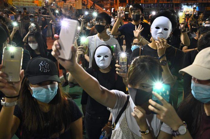 Demonstranten dragen maskers en gebruiken hun telefoon als zaklamp tijdens een flash mob in het district Sham Shui Po, een dag nadat gisteren in Hongkong een verbod op gezichtsbedekking is ingesteld