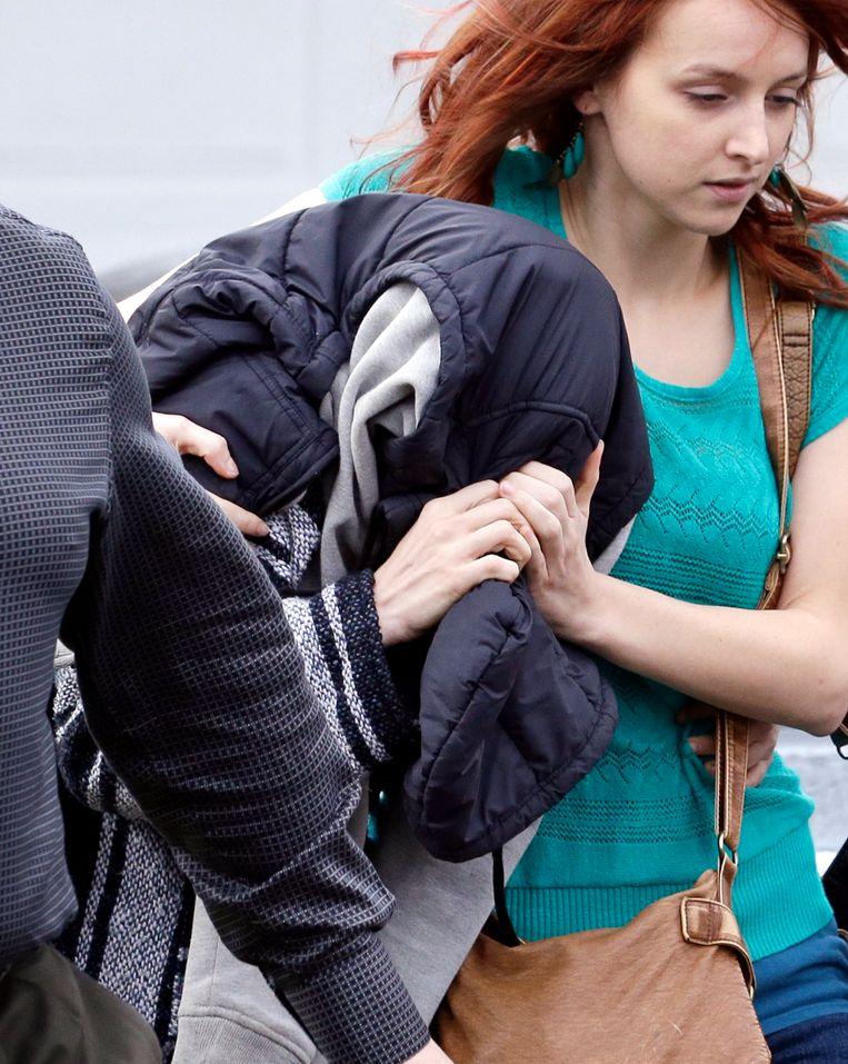 Een vrouw van wie gedacht wordt dat het Amanda Knox is, verlaat met een jas over haar hoofd het ouderlijk huis van Knox na de uitspraak van de Italiaanse rechter. Beeld AP